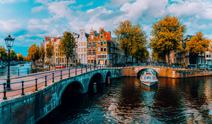 Panorama of Amsterdam. Famous canals und bridges at warm afternoon light. Netherlands