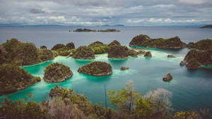 Panorama of Pianemo island overgrown with jungle plants, surrounded by shallow turquoise colored ocean lagoon. White clouds moving on horizon in background. Raja Ampat, West Papua, Indonesia
