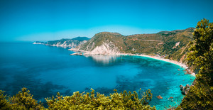 Panorama View to Petani beach with transparent and crystal clear blue mediterranean sea water in picturesque bay, Kefalonia island, Greece