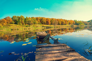 Panoramic view of a lakeshore with broken wooden pier in front. Beautiful rural nature.
