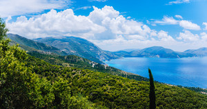 Panoramic view of amazing coastline on Kefalonia Island. Picturesque landscape, colorful Ionian sea, white clouds floating over mountains. Greece