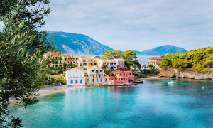 Panoramic view of Assos village in Kefalonia, Greece. Turquoise blue colored water in Mediterranean sea and beautiful cute colorful local houses