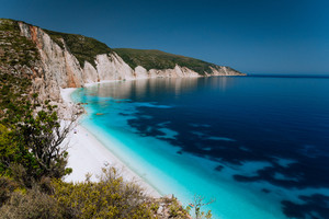 Panoramic view of Fteri beach, blue lagoon with rocky coastline, Kefalonia, Greece. Calm clear blue emerald green turquoise sea water with dark deep pattern