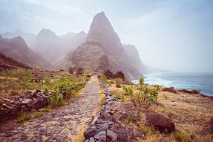 Panoramic view of stony hiking path to Ponta do Sol over amazing arid Aranhas valley with huge mountain peak and house ruins. Santo Antao Island, Cape Verde