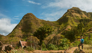 Panoramic view of woman tourist with blue backpack making photo of landscape in Mountains of Santo Antao island, Cabo Verde