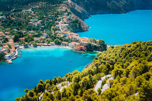 Panoramic view to Assos village Kefalonia. Greece. White lonely yacht in beautiful turquoise colored bay lagoon water surrounded by pine and cypress trees along the coastline