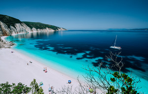 Panoramic view to remote beach wiht lonely white catamaran yacht drift in clear blue Caribbean like sea water. Tourists leisure activity on the beach with azure colored shallow lagoon