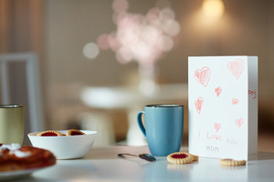 Paper greeting card for mother, mug with drink and biscuits on table
