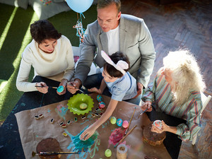 Parents, their son and senior female painting Easter eggs together