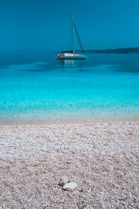 Pebble beach and white catamaran yacht boat in calm azure blue lagoon water at anchor
