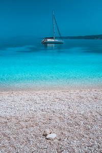 Pebble beach and white catamaran yacht boat in calm azure blue lagoon water at anchor