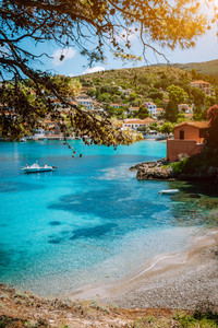 Pebble beach with transparent turquoise sea water. Assos village, Kefalonia Greece. Sun beams appear through green pine trees branches