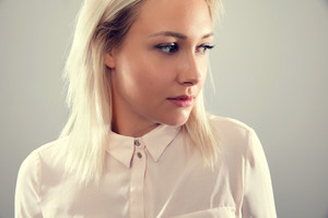Pensive beautiful female blonde model in shirt looking away from camera