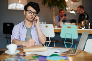 Pensive young man calling while concentrating on creative work
