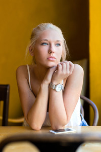 Pensive young woman at cafe looks out the window