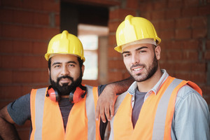 People working in construction site. Portrait of happy men at work in new house inside apartment building. Professional workers looking and smiling at camera as co-workers and friends