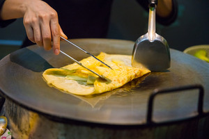 Person Preparing Pineapple Pancake At Market Stall