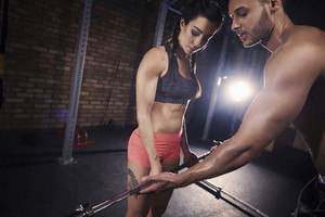 Personal trainer guiding woman at gym