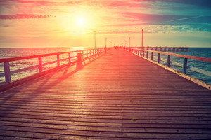 Perspective view of wooden pier over sea. Palanga city at sunset in autumn, Lithuania