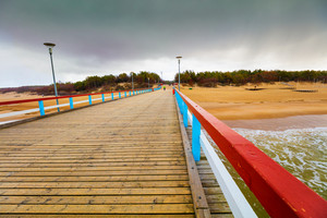Perspective view of wooden pier over sea. Palanga in rainy autumn day, Lithuania