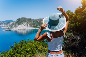 Petani beach Kefalonia. Young woman holding blue sun hat enjoying beautiful panorama of blue bay lagoon surrounded by steep cliff coastline. Greece