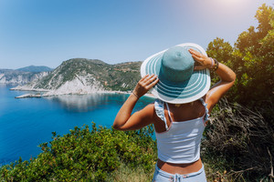 Petani beach Kefalonia. Young woman holding blue sun hat enjoying beautiful panorama of blue bay lagoon surrounded by steep cliff coastline. Greece