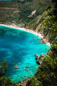 Petani beach on hot sunny summer day. View to Petani bay with transparent and crystal clear blue azure mediterranean sea water in beautiful lagoon, Kefalonia island, Greece