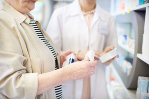 Pharmacist advising senior woman on medicine