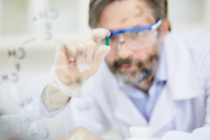Pharmacologist in gloves holding green pill, new vaccine created in laboratory