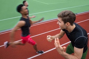 Photo of a trainer screaming near young multiethnic athlete men run on running track outdoors.