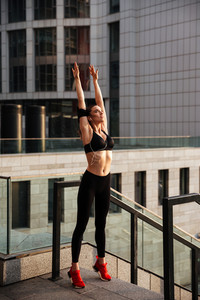 Photo of amazing young sports woman standing with earphones outdoors and looking aside while stretching.