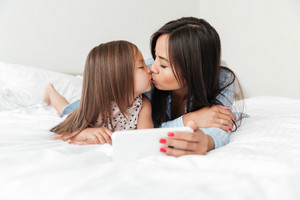 Photo of amazing young woman with little daughter at home indoors using mobile phone and kissing.