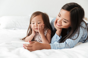 Photo of amazing young woman with little daughter at home indoors using mobile phone.