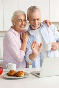 Photo of cheerful mature loving couple family standing at the kitchen drinking tea eating pastries while using laptop computer. Looking aside.