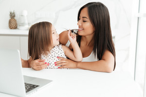 Photo of cheerful mom sitting at the table with little cute asian girl at home indoors using laptop computer. Looking aside.
