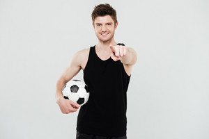 Photo of cheerful young sportsman with foot ball standing isolated over white background. Looking at camera pointing.
