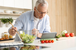 Photo of concentrated mature man wearing glasses standing at the kitchen cooking salad using tablet computer. Looking aside.
