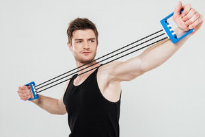Photo of concentrated young sportsman make sport exercises isolated over white background. Looking aside.
