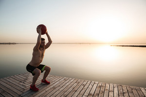 Photo of concentrated young sportsman make sport exercises with ball at the beach. Looking aside.