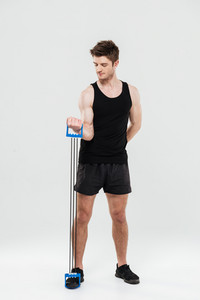 Photo of concentrated young sportsman standing isolated over white background make sport exercises. Looking aside.