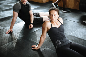 Photo of fitness group of people sitting on floor make sports exercises indoors.