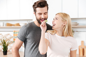 Photo of funny young loving couple standing at kitchen and cooking together. Looking aside.