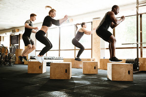 Photo of group of multiethnic sports strong people make sport exercise jumping. Looking aside.