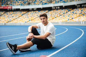 Photo of handsome young sports man sitting at the stadium outdoors looking camera.