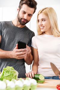 Photo of happy young loving couple standing at kitchen and cooking together using mobile phone. Looking aside.