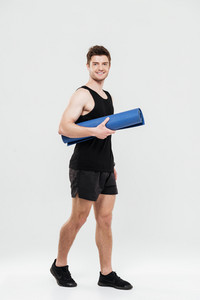 Photo of happy young sportsman standing isolated over white background holding fitness rug. Looking at camera.
