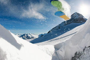 Photo of jumping snowboarder over mountainside on winter resort