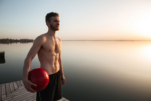 Photo of serious young sportsman standing with ball at the beach. Looking aside.