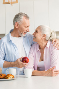 Photo of smiling mature loving couple family standing at the kitchen. Man holding apple. Looking at each other.