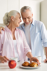 Photo of smiling mature loving couple family standing at the kitchen near apple and pastries. Looking aside.